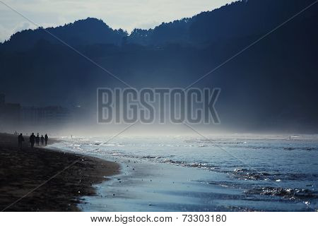 Amazing dark silhouette of mountains around bay, cold evening on the ocean beach, wet sand