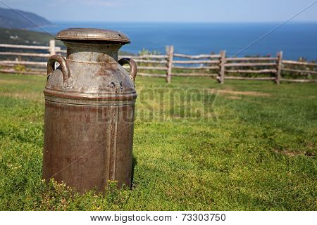 Old rusty milk churn in a field, with rustic wood fence and the sea in the background.