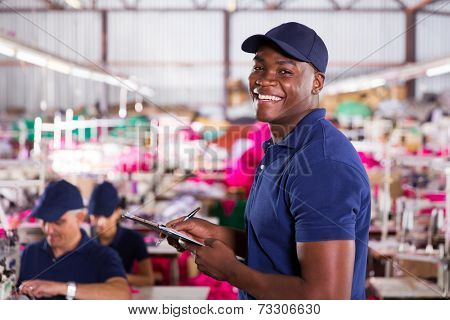 cheerful african textile factory worker in production area