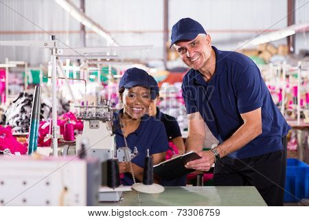 portrait of african machinist with senior foreman in clothing factory