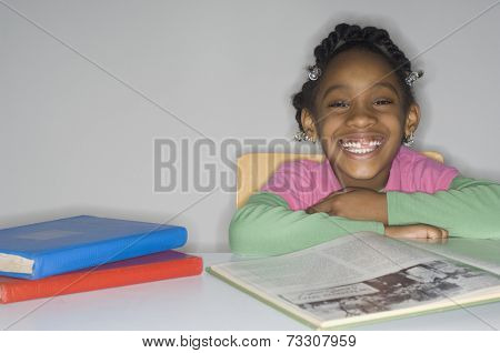 African girl at table with school books