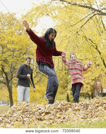 Multi-ethnic family playing in autumn leaves