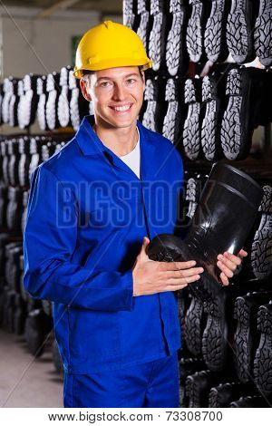 smiling factory worker holding rubber-boot