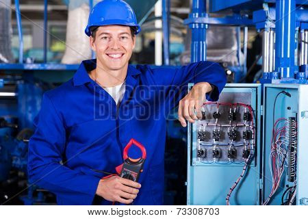 portrait of industrial electrician with insulation tester in factory