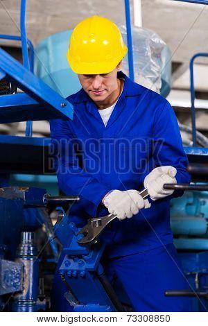 skilled young mechanic repairing factory machine