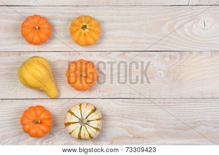 Gourds and pumpkins from a high angle on a white rustic wooden table. Horizontal format with copyspace.