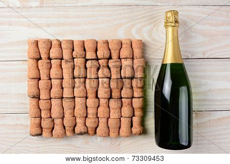 High angle shot of a bottle of champagne laying next to a large group of corks arranged in rows on a whitewashed wood table.