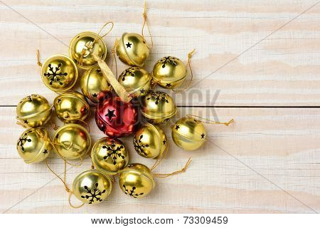 High angle shot of a group of Christmas jingle bells on a white wood table. Horizontal format  with one red bell surrounded by a lot of smaller gold bells.