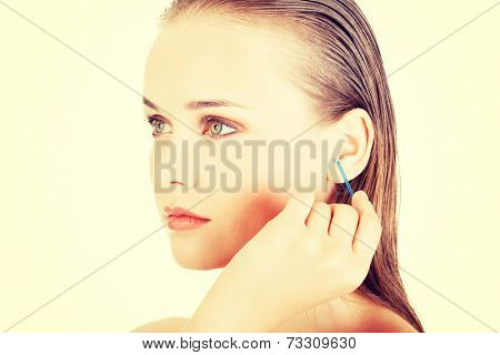 Happy woman cleans her ear