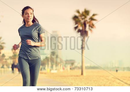 Running woman jogging on beach boardwalk. Healthy lifestyle girl runner training outside working out. Mixed race Asian Caucasian fitness woman exercising outdoors.