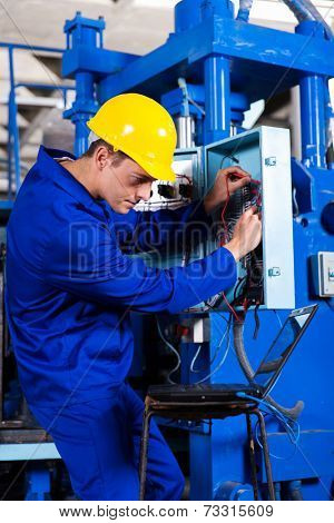 industrial technician repairing modern computerized machine in factory