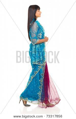 side view of indian woman in saree walking on white background