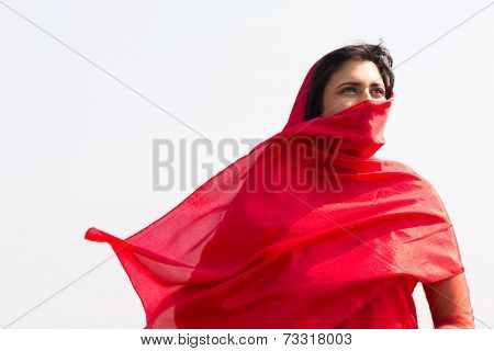 thoughtful indian woman in sari covering her face with veil