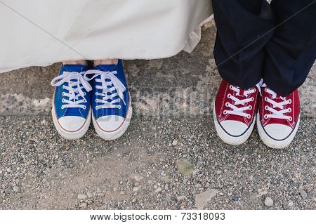 Bride and groom' legs in color gym shoes