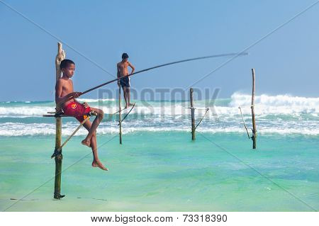 UNAWATUNA, SRI LANKA - MARCH 9, 2014: Young stilt fishermen at Hikkaduwa Beach. Most real stilt fishermen have been long gone. Today it's mainly young boys posing as stilt fishermen for tourists.