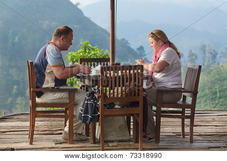 ELLA, SRI LANKA - MARCH 3, 2014: Tourist couple having breakfast at bungalow terrace with amazing view on tea plantations in background. Tea plantations are vital part of Sri Lankan economy since 1850