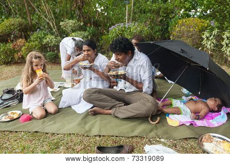 KANDY, SRI LANKA - FEBRUARY 26, 2014: Local Sri Lankan family, eating with hands, invite young tourist to share their outdoor picnic. Hospitality and sharing is custom in this very friendly country.