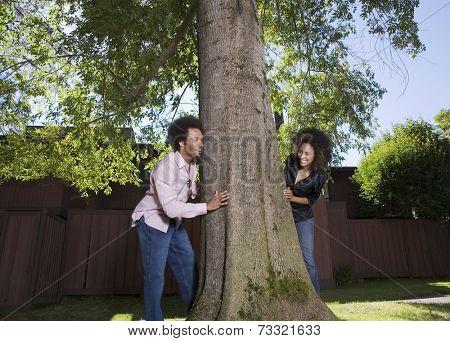 African couple peeking around tree
