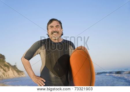Hispanic man holding surfboard