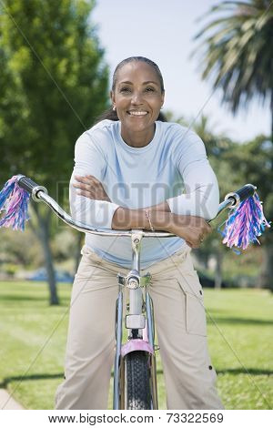 Mixed Race woman on girl's bicycle