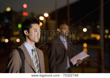Multi-ethnic businessmen outdoors at night