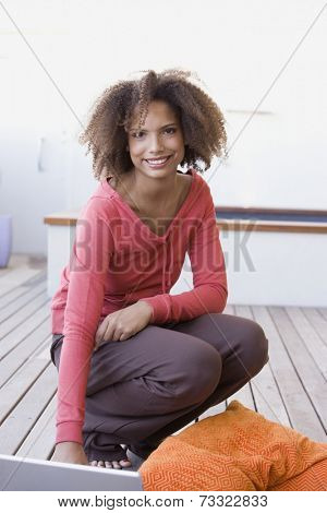 African woman crouching on deck