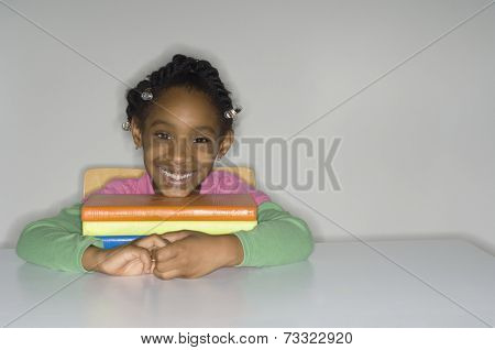 African girl with stack of school books