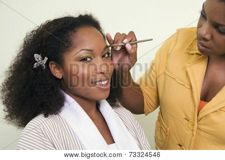 African woman having makeup applied