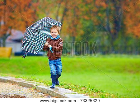 Happy Boy Running Under An Autumn Rain
