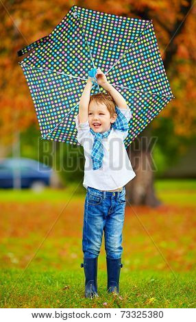 Happy Boy Playing Under An Autumn Rain