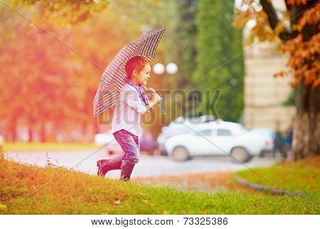 Cute Boy Enjoying An Autumn Rain In City Park