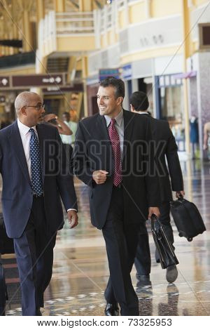 Smiling businessmen walking in airport