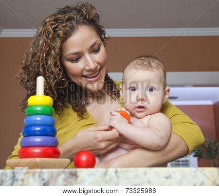 Hispanic woman playing with daughter