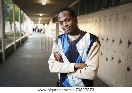 African teenage boy standing in school hallway