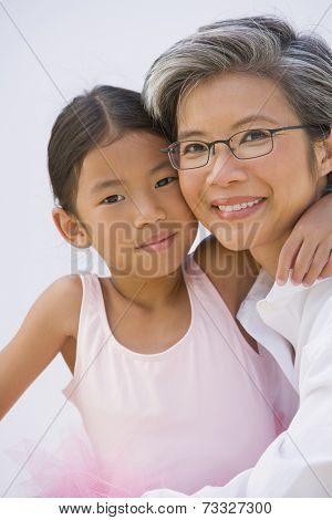 Asian mother and daughter in ballet outfit hugging