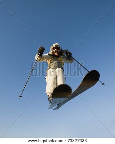 Mixed race woman on skis in mid-air