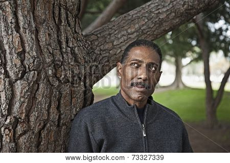 African man leaning on tree in park