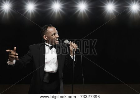 African American man in tuxedo singing into microphone