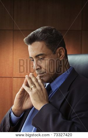Hispanic businessman thinking