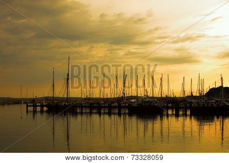 Docked Yachts In Marina At Sunset