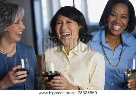 Multi-ethnic women drinking wine