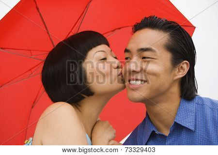 Asian woman kissing boyfriend on cheek