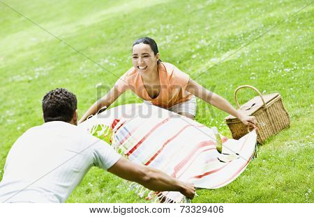 Hispanic couple laying out picnic blanket