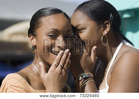 African teenaged girls telling secret