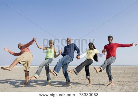 Multi-ethnic friends holding hands and kicking