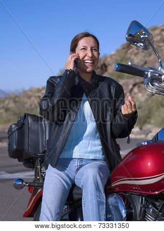 Hispanic woman on motorcycle talking on cell phone