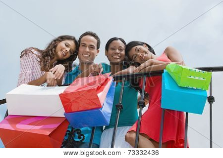 Hispanic friends holding shopping bags