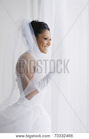 Hispanic bride looking out window