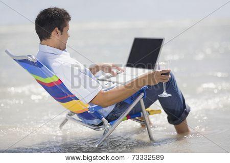 Hispanic man in beach chair with laptop