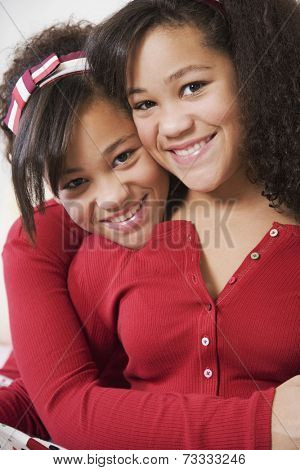 African twin sisters hugging